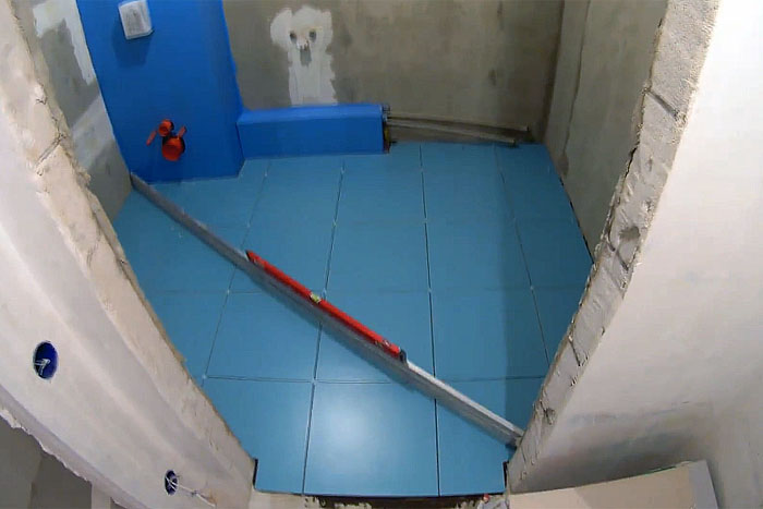 Укладка напольной плитки, проверка строительным уровнем