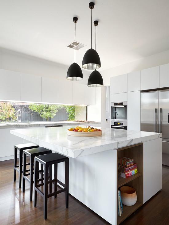 Дизайн интерьера кухни в стиле минимализм: освещение обеденной зоны светильниками с контрастными чёрными плафонами
