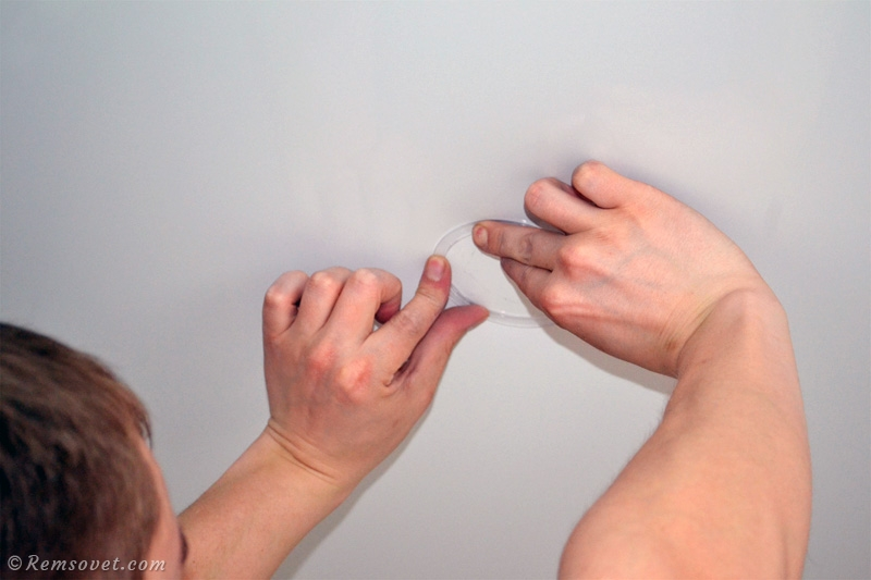 Приклеиваем пластиковое кольцо к поверхности натяжного потолка