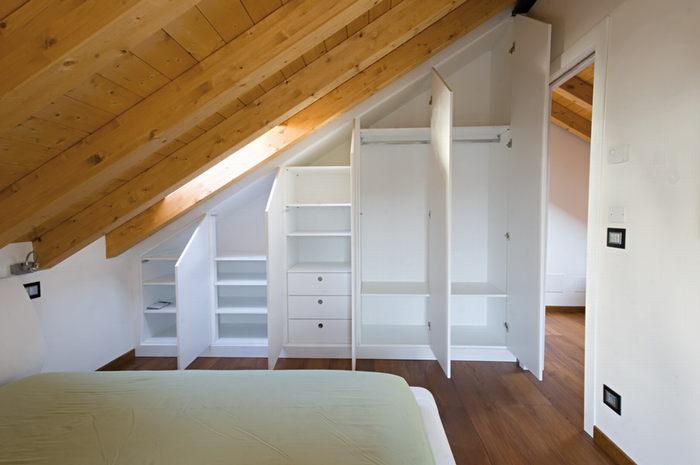 Интересное решение с вещевыми шкафами под скатной крышей помогает сэкономить место