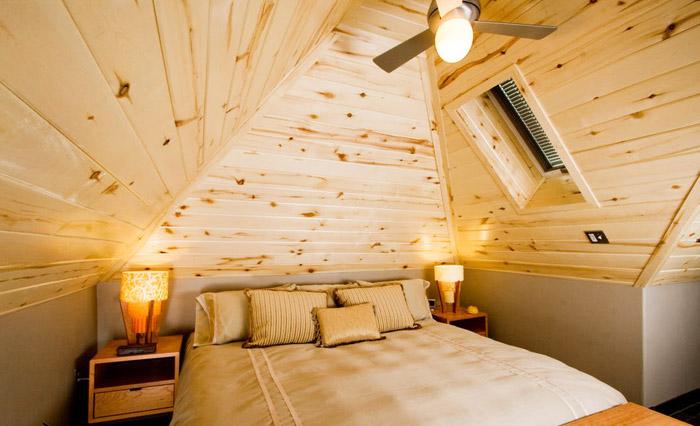 Отделка стен и потолка мансарды деревом позволяет сделать спальню уютной, натуральной и экологичной