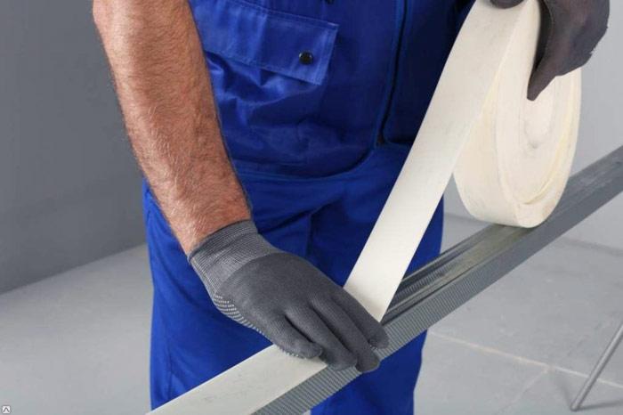 Наклеивание уплотнительной ленты к тыльной стороне направляющего профиля